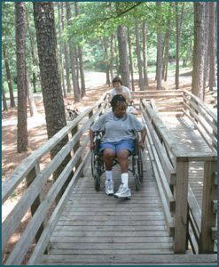 alt text= person helps person in wheelchair on camp ramp