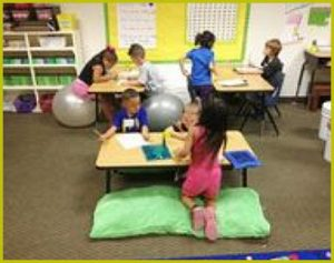 alt text= children in classroom with soft surfaces, large balls, learning areas
