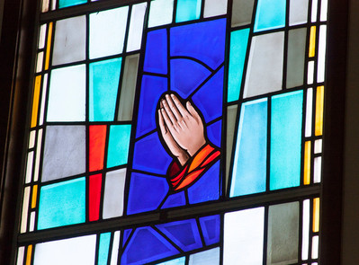 Alt text=hands pray in stained glass