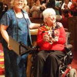 alt text = Woman gives woman in wheelchair a disAbility award