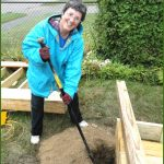 smiling woman digs post hole for a ramp