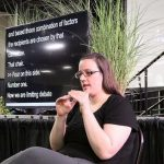 woman using American Sign Language, in the background is a screen with captions