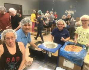 Happy people with hairnets put grain into bags