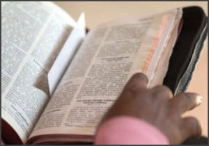 Hand placed on open Bible