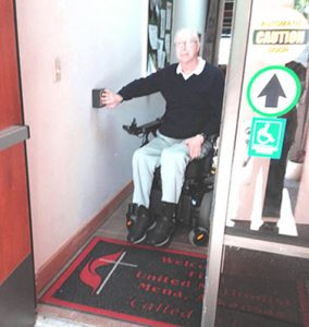 Man in wheelchair uses auto door opener