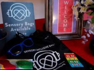 Sensory kit from Faith UMC: a bag, labeled, sunglasses and fidgets can be seen; there is also a sign on a table explaining the kit.